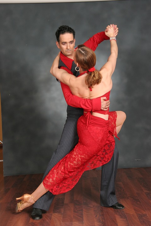 Salsa Dancing couple in red dress and grey outfit